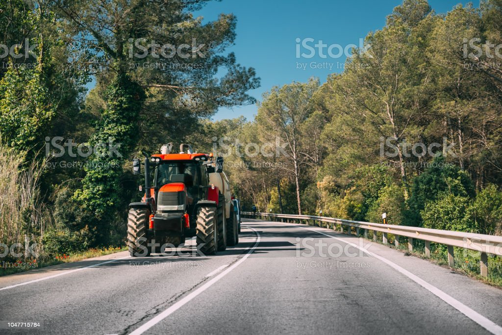 Tractor With Fertilizer Applicator With Tank In Motion On Country Road In Europe. stock photo
