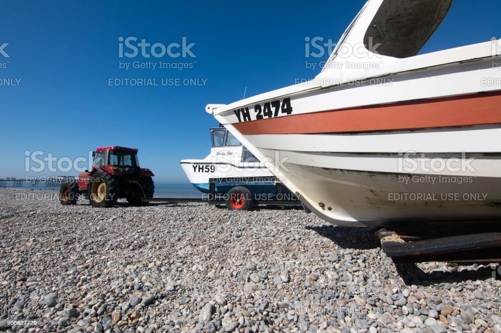 Tractor with fishing boats on beach stock photo