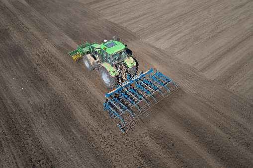 Aerial view of a modern tractor with front and rear mounted cultivator working in field.
