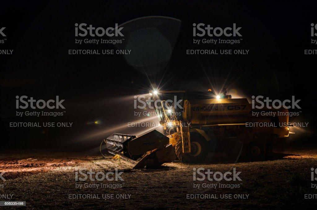 Trator com luzes acesas à noite, após a colheita de soja - foto de acervo