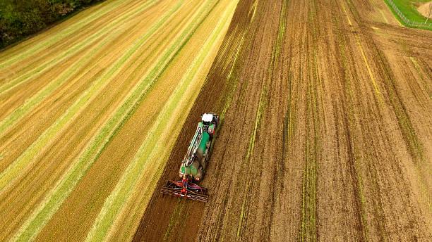 traktor mit flüssigkeit gülle spritzgerät auf feld-luftaufnahme - aerial view soil germany stock-fotos und bilder