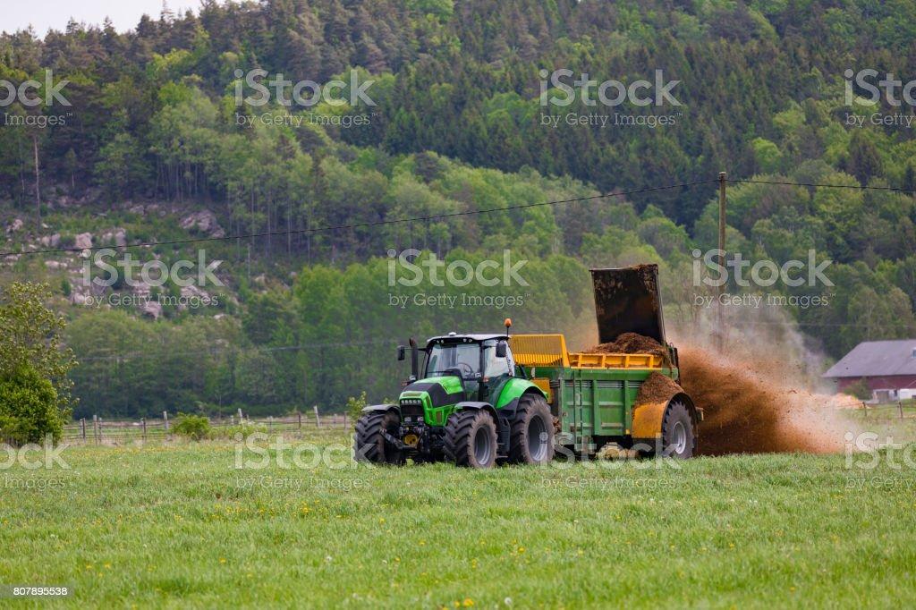 Traktor med organiska gödselspridare bildbanksfoto