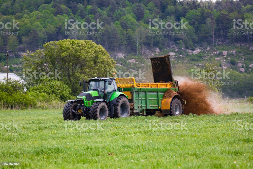 Tractor with organic fertilizer spreader stock photo
