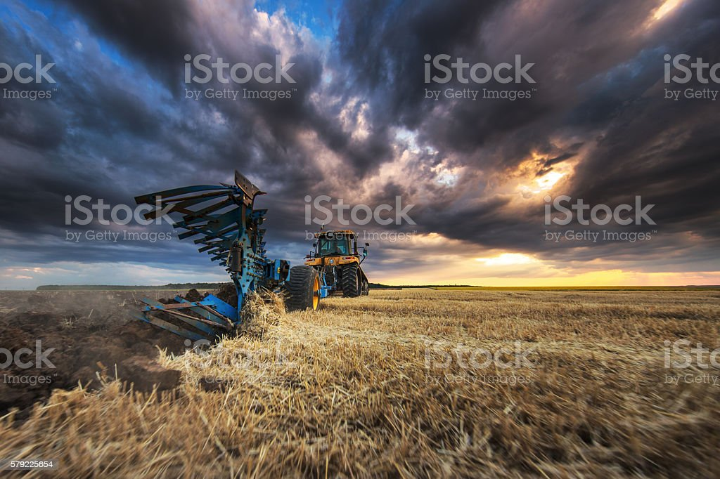 Tractor with Plough, Plowing in a Field - foto de stock