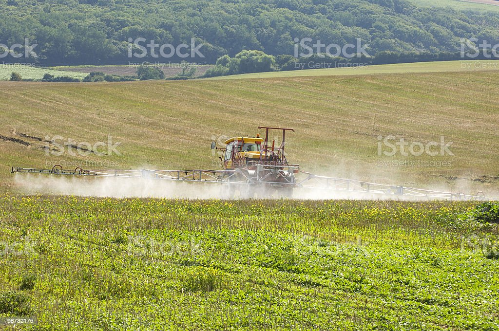 Tractor with spray rig spraying fertilizer onto field royalty free stockfoto