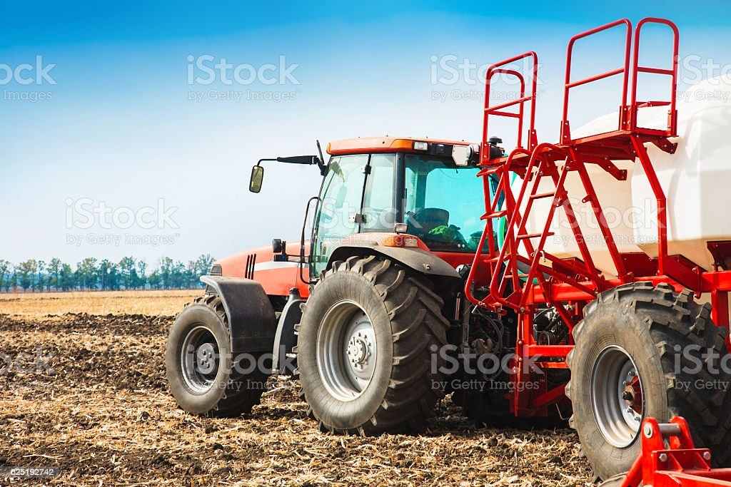 Tractor with tanks working in the field. stock photo