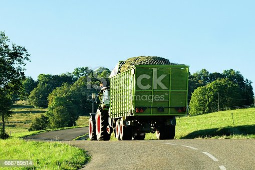 Tractor with trailer full of hay on the road in Bourgogne-Franche-Comte region in France.