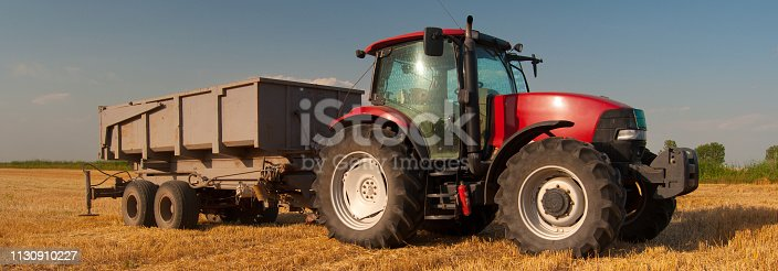 Modern agricultural tractor with trailer on the wheat field after harvest.