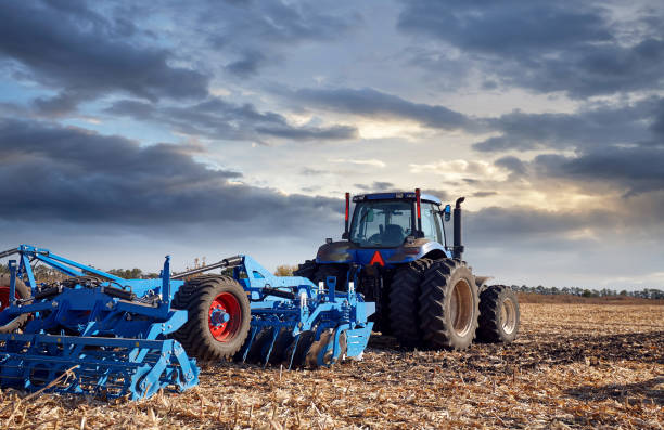 Tractor working in the field at sunset Tractor working on the farm, a modern agricultural transport, a farmer working in the field, fertile land, tractor on a sunset background, cultivation of land, agricultural machine agricultural machinery stock pictures, royalty-free photos & images