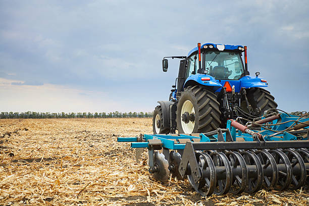 Tractor working in the field in autumn stock photo