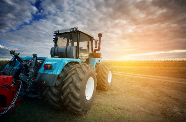 Tractor working in the field in the background of the sunset stock photo