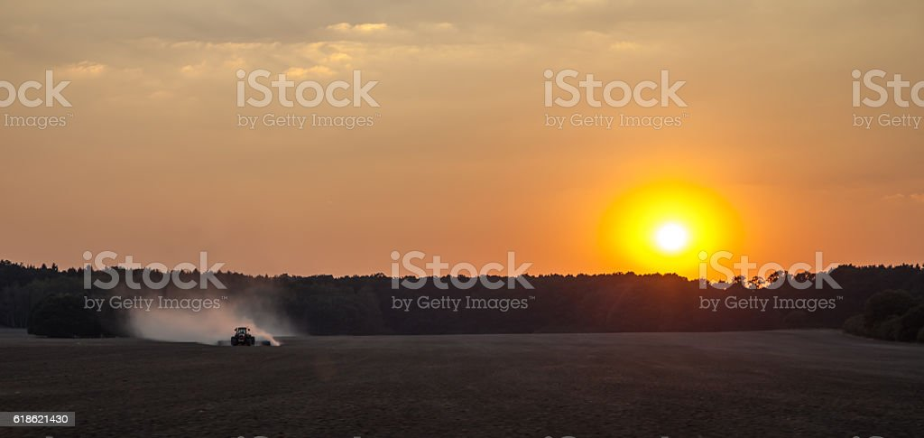 Tractor working the field an the sunset stock photo