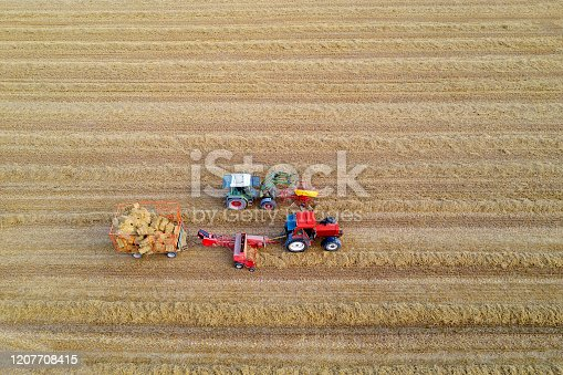 Two tractors baling, collecting and loading hay bales on hay wagon in harvested field, aerial view.