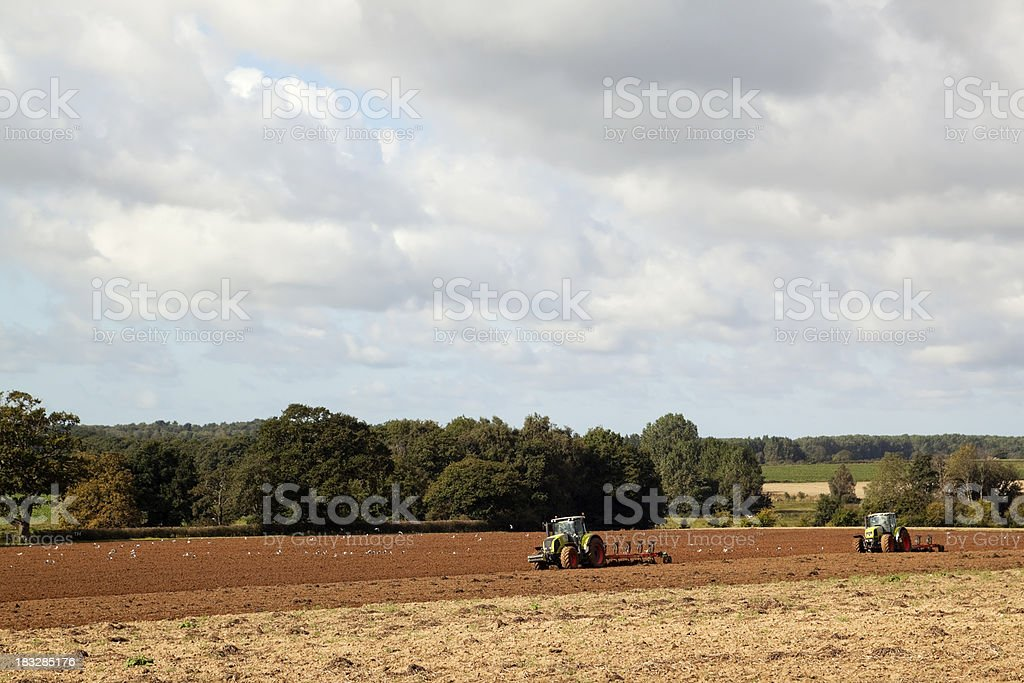 Tractors ploughing in a Norfolk field royalty-free stock photo