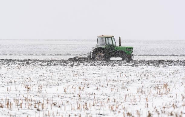 Traktoren pflügen Stoppelfelder im Winter – Foto