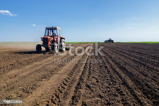 Tractors sowing on agricultural field on a beautiful sunny spring day.