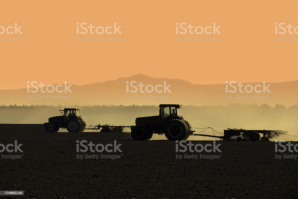 Tractors working fields silhouetted at sunrise stock photo