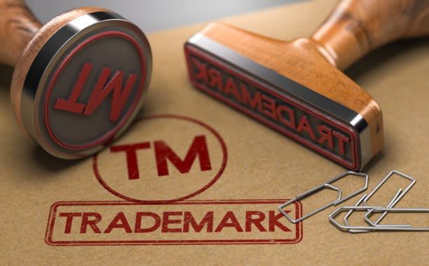 Trademark Registration Concept 3D illustration of two rubber stamps with the word trademark and the symbol TM over brown paper background. Trade-mark Registration Concept intellectual property stock pictures, royalty-free photos & images