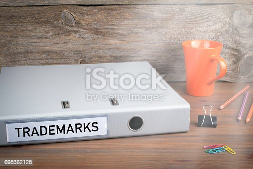 850881300 istock photo Trademarks. Folder, Coffee Mug and colored pencils on wooden office desk 695362128