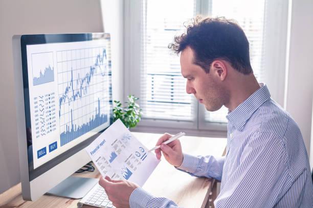 trader analyzing financial report and trading charts and computer screen - rapporto finanziario foto e immagini stock
