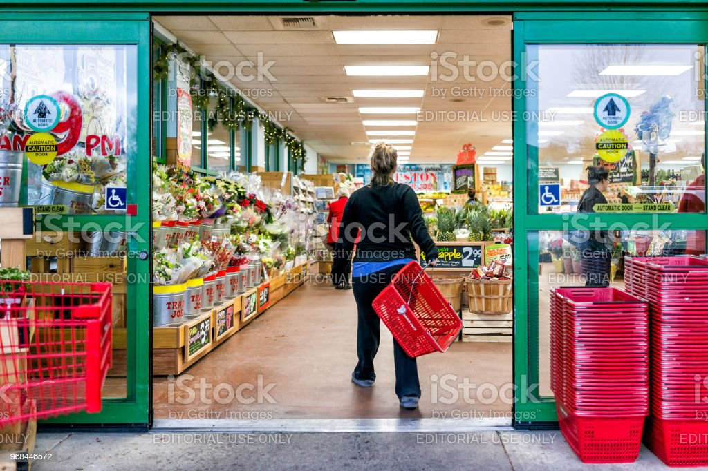 Trole de cliente Trader Joe compras cesta carregando carrinhos por portas de entrada de loja fora mulheres, vasos de flores de inverno, jardinagem plantas abacaxi em Virgínia - foto de acervo