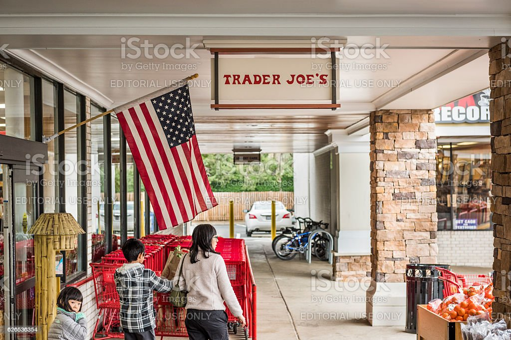 Trader Joes grocery store entrance with sign and American flag stock photo