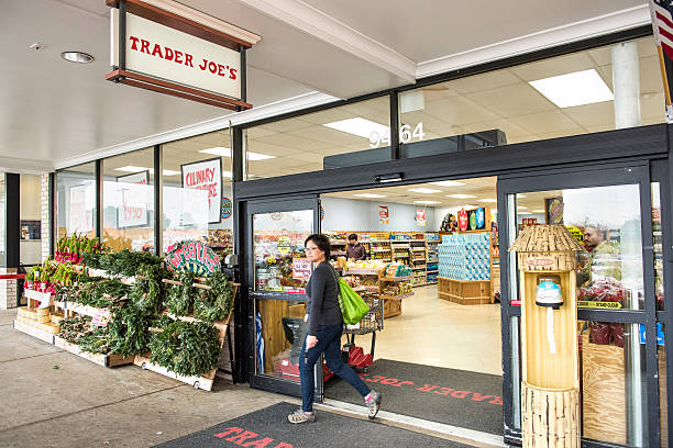 Trader Joes grocery store entrance with sign Fairfax, USA - November 25, 2016: Trader Joes grocery store entrance with sign, display and view on interior with woman walking out entrance sign stock pictures, royalty-free photos & images