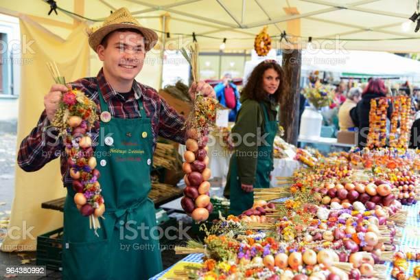 Foto de Comerciante Com Tranças De Cebola No Mercado Tradicional Em Weimar Alemanha e mais fotos de stock de 25-30 Anos
