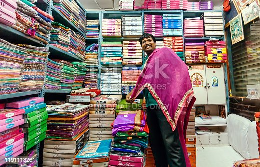 Bangalore, India: Trader working with female fashion, colorful scarfs and traditional sari in textile store on February 12, 2017. With popul. 8.52 million, Bangalore is third most populous indian city