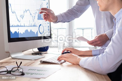 istock Traders discussing trading strategy, profit and ROI, stock market charts 956414388