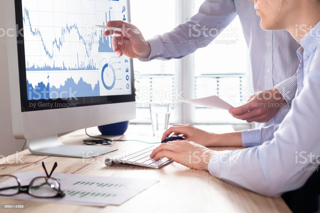 Traders discussing trading strategy, profit and ROI, stock market charts stock photo