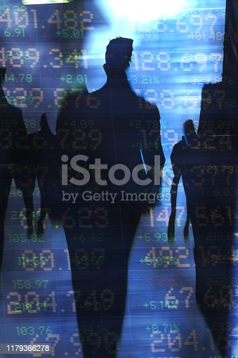 Abstract image of traders in financial district with trading screen data, light reflections and blurred movement.