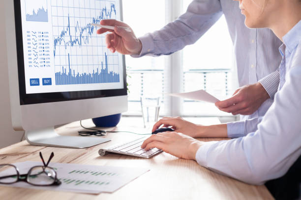 Traders with forex trading charts and graphs on computer screen - foto stock