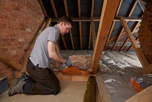 Tradesman fits insulation in attic stock photo