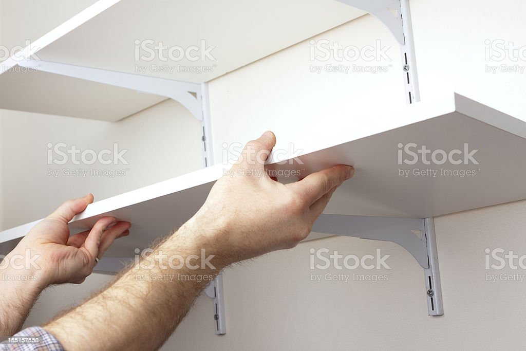 A tradesman installing hanging shelves royalty-free stock photo