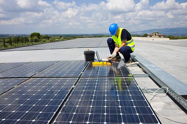 Tradesman installing solar panels on roof stock photo
