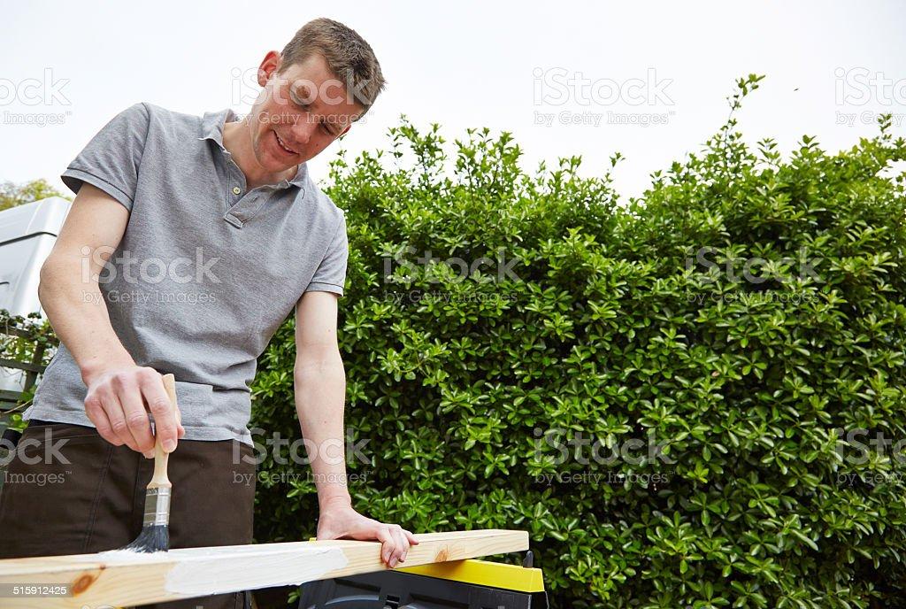 Tradesman paints a length of wood stock photo