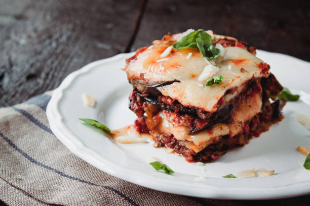 tradicional parmigiana di melanzane: baked eggplant - italy, sicily cousine.baked eggplant with cheese, tomatoes and spices on a white plate. a dish of eggplant is on a wooden table - melanzane foto e immagini stock
