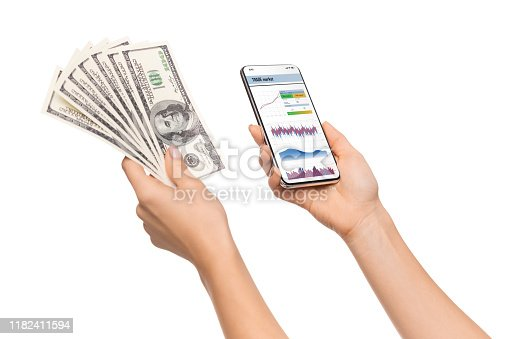 Online exchange. Trading app opened on smartphone and cash in female hands over white background