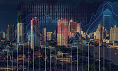 Trading graph on the cityscape at night and world map background,Business financial concept