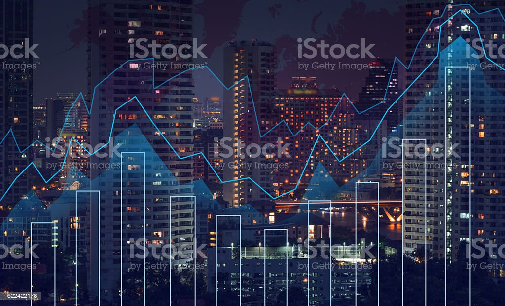 Trading graph on the cityscape at night and world map stock photo