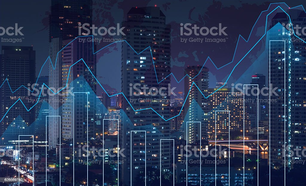 Trading graph on the cityscape at night and world map​​​ foto
