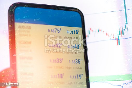 Trading stock or forex online with application on smartphone / Businessman trading stocks with statistic analysis price table market financial on mobile phone finance data and technology