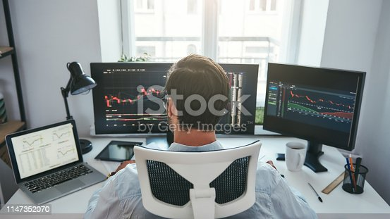 Trading stocks online. Back view of young businessman or trader working with graph and charts on computers at his modern office. Forex market. Trade concept. Investment concept