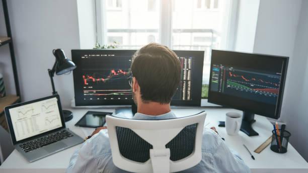 株をオンラインで取引する。彼の近代的なオフィスでコンピュータ上のグラフやチャートを扱う若手ビジネスマンやトレーダーのバックビュー - 投資家 ストックフォトと画像