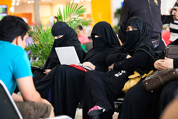 """Tradition and modernity """"Kuala Lumpur, Malaysia - April 3, 2011: Three Muslim women in burqas. Two are using modern laptops"""" kuala lumpur airport stock pictures, royalty-free photos & images"""