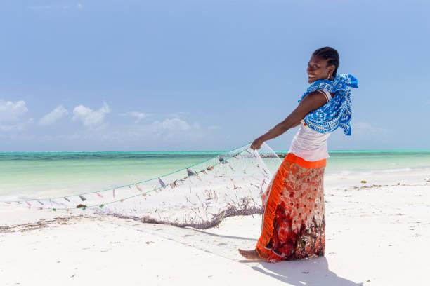 Traditionelle afrikanische lokale lande Fischerei am Strand von Paje, Sansibar, Tansania. Traditionell gekleidete einheimische Frau zieht Fischernetz, fangen kleine Fische. – Foto