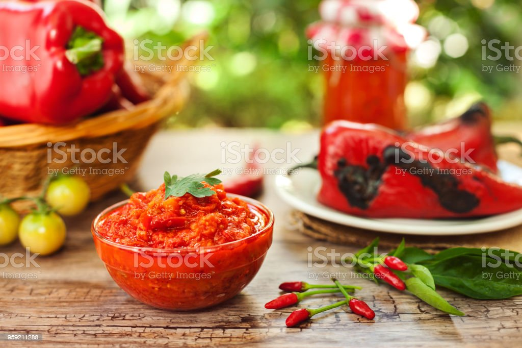 Traditional ajvar in bowl with chili peppers stock photo
