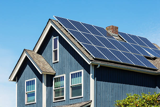 Traditional American Home with Modern Solar Panels on Roof Photo of a small--town American home with energy-efficient solar panels on the roof. solar panels photos stock pictures, royalty-free photos & images