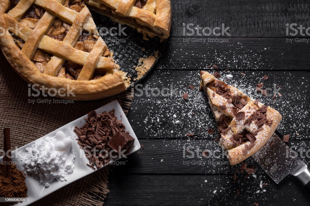 Kitchen table with a whole apple pie and one slice on a knife, with...